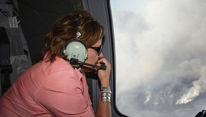 New Mexico Governor Susana Martinez looks out the window of a Black Hawk helicopter flying over the Dog Head Fire Thursday, June 16, 2016 in Albuquerque. Firefighters struggled Thursday to make progress against a fast-moving wildfire in central New Mexico as it consumed tinder dry forest, sent up a towering plume of smoke that could be seen for miles, and forced more residents from their homes.