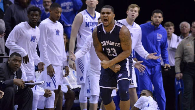 Monmouth's Austin Tilghman celebrates in front of the Memphis bench as the Hawks beat the Tigers, 82-79.