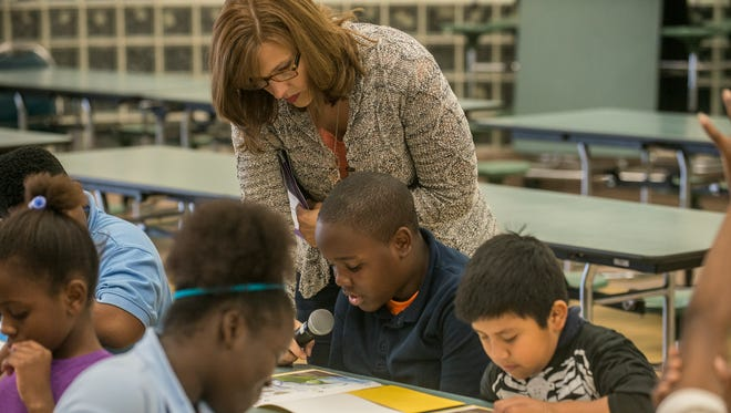 Ashley Henderson of the Alabama Clean Water Partnership holds the microphone for a student reading about the water cycle. Fifth-grade members of the Blue Planet Defenders met Thursday, Oct. 29, 2015, at T.S. Morris Elementary School in Montgomery, Ala.