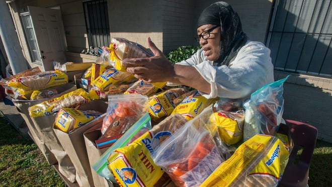 Christine Buford helps pack bags of food to be given away Saturday morning, Dec. 12, 2015, at the Muslim Center of Montgomery, 4340 Court St.