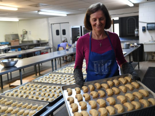 Pauline Giannopoulos pulls wedding cookies out of the oven as she and the women of St George Greek Orthodox Church make traditional pastries on Wednesday in preparation for the Greek Pastry Sale.