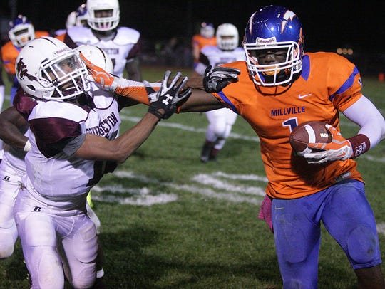Ryquell Armstead (right) carries the ball for Millville during a game against Bridgeton in 2014.