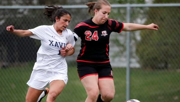 Xavier High School's Ellie Arndt fights for control of the ball with Seymour High School's Hannah Schultz Tuesday, May 8, 2018, in Appleton, Wis. Xavier defeated Seymour 4-0.