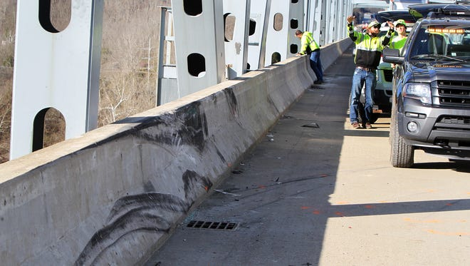 Workers from the Kentucky Cabinet of Transportation inspect the spot where a car ran off the eastbound lanes of the  I-275 Combs-Hehl Bridge and plummeted into the Ohio River.