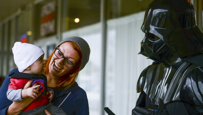 Five-month-old Oliver Kantor reacts as his mother, Brandy Alexander, holds him up to a person dressed as Darth Vader during the 2015 Star Wars Day party at Totally 80s Pizza in Fort Collins.