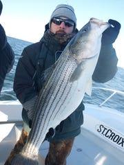 Paul Dejohn holding the 20 pound striped bass he caught while fishing with Captain Alex Majewski of Lighthouse Sportsfishing.