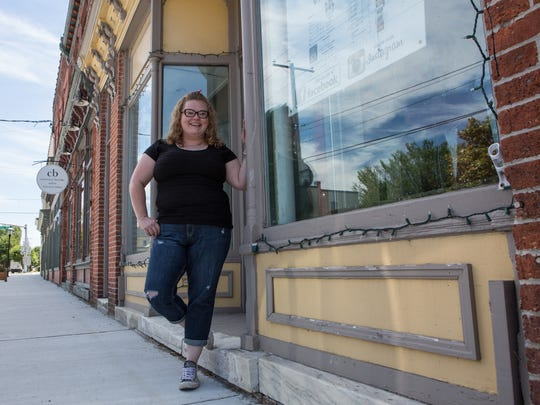 Daily Brew Coffeehouse owner, Lori McAllister, poses for a photo outside her Washington Street store on Tuesday, June 14, 2016.