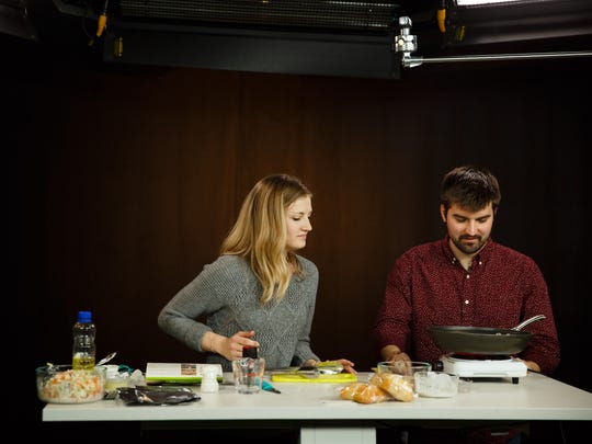 Register Producer Lauren Ehrler and reporter Aaron Young try the Shitake Mushroom and Chicken Sandwich Hy-Vee meal kit on Tuesday, April 17, 2018, in Des Moines.