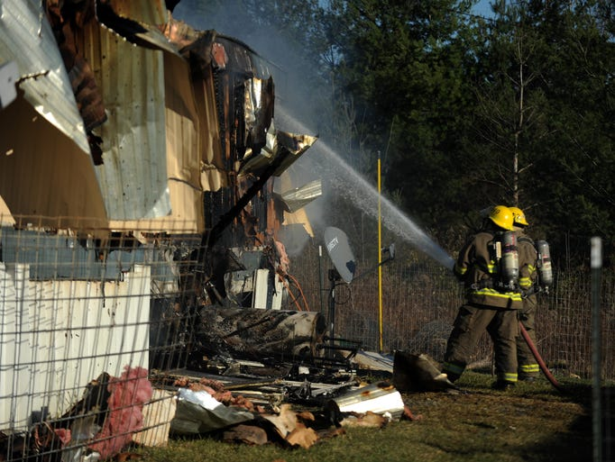 Firefighters spray water on a burning mobile home Tuesday
