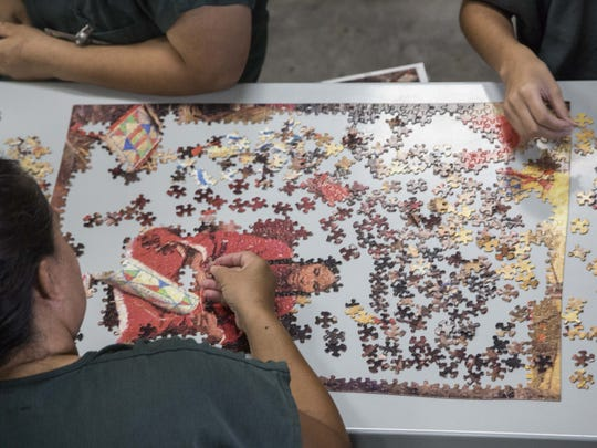 Women keep themselves busy with a jigsaw puzzle in their cell at the Eloy Detention Center facility in 2015.