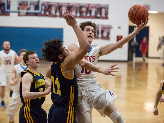 St. Clair sophomore Ben Davidson takes a shot over a host of Port Huron Northern defenders during a basketball game Wednesday, March 2, 2016 at St. Clair High School.