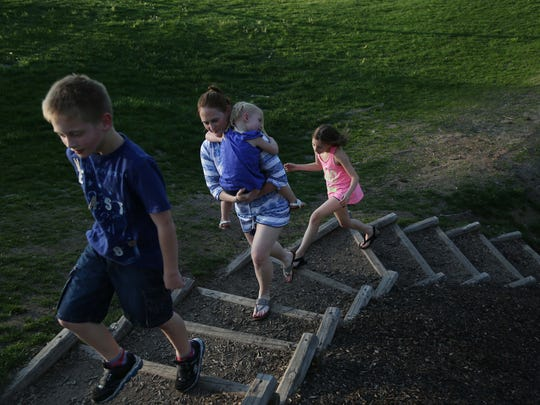 Jessica Hoenicke climbs the stairs with her children Cayden, 9, Jocilynn, 3, and Giana, 10, at Walker Johnston Park in Urbandale.