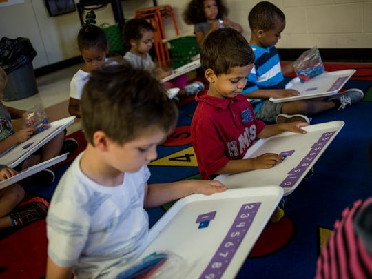 Alijah Bell, 5, works on a math exercise with other
