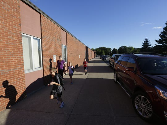 A student runs inside on the first day of school Thursday in Amherst.