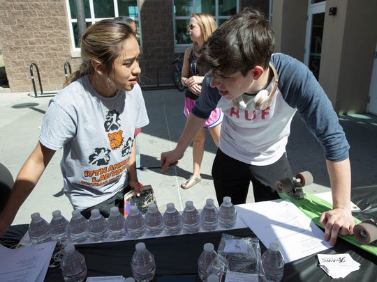 Monic Jimenez,left, and Bryce Larson,right, both freshman at New Mexico State University, fill out a survey about binge drinking at a booth set up out side the James B. Delamater Activities Center to aware students of the dangers of binge drinking before spring break starts, Wednesday, March 15, 2017.