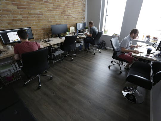 Graphic designers work in their creative space.  Quill