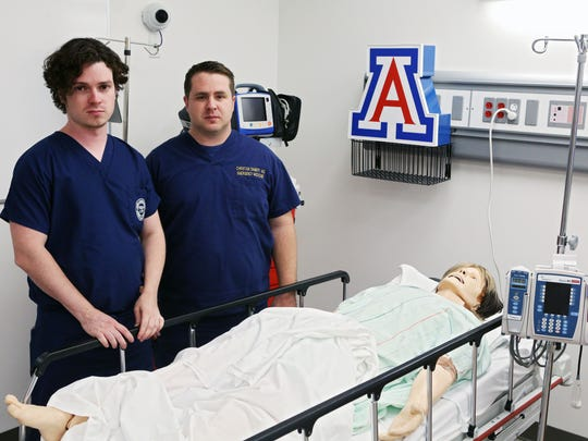 Drs. Jeff Tully (left) and Christian Dameff, both of whom are also hackers, stand over a dummy used in simulations of cyberattacks on medical devices. Dameff says the time to figure out how to prevent such attacks is now, not after one has occurred.