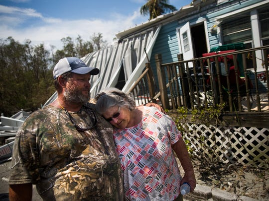 Robby Daffin consoles his mother, Nancy Daffin, as she returns to her destroyed home on Plantation Island for the first time after Hurricane Irma in Everglades City, Fla.