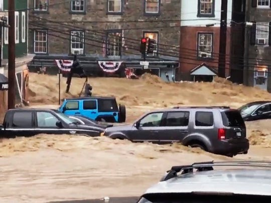 Water rushes through Main Street in Ellicott City, Md., on May 27, 2018.