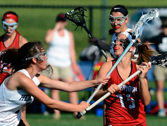 Susquehannock's Morgan LeBlanc is hit by Hempfield's Sophie Spangler as she attempts a shot on goal in the first half of the District 3 girls' lacrosse semifinals at Hershey High School on Tuesday. Hempfield won the match, 16-12.