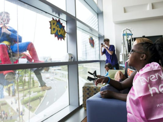 Ahzhanae Kirkland, 7, of Lancaster (left) and Alexia Heilman, 11, of Manchester, watch as Superman (Mark Barnaba) and other costume-clad employees of Northeastern Building Maintenance descend from the roof of the Penn State Hershey Children's Hospital to greet children at the hospital on Wednesday. Window washing is just their day job.