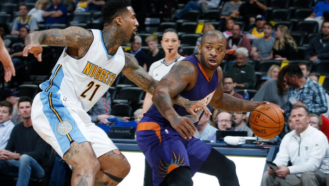 Phoenix Suns forward P.J. Tucker looks to pass as Denver Nuggets forward Wilson Chandler defends in the first half of an NBA preseason game on Friday, Oct. 16, 2015, in Denver.