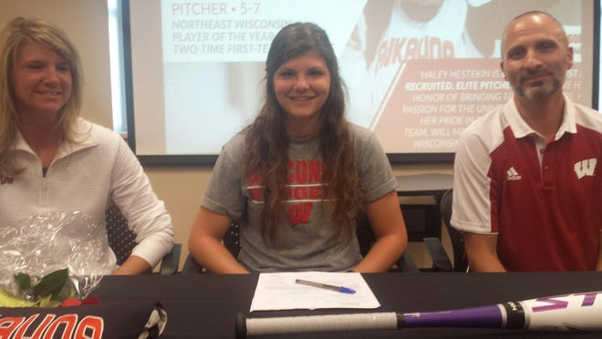 Kaukauna softball standout Haley Hestekin is joined by her parents after signing a letter of intent Wednesday to play softball at the University of Wisconsin.