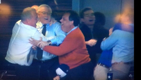 Gov. Chris Christie (right, orange sweater) joins in the jubilation with Dallas Cowboys owner Jerry Jones on Sunday.