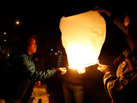Katrina Johnson helps hold a paper lantern Thursday, March 2, 2017 as family and friends try to launch the memorial lanterns into the air by the river to mark the one year anniversary of Kedarie Johnson's death in Burlington, Iowa. The group had trouble getting the lanterns to stay lit in the wind and cold and postponed the launch until Saturday.