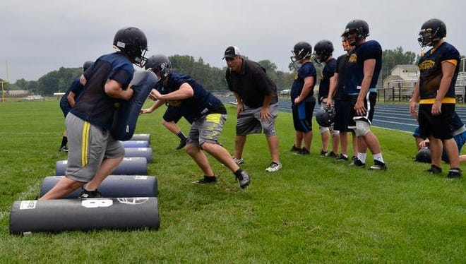 Port Huron Northern's defense runs through drills Aug. 20 during football practice at Port Huron Northern High School.