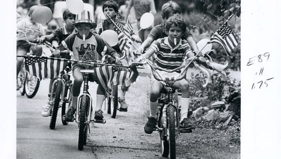 Children ride bikes during a Fourth of July parade