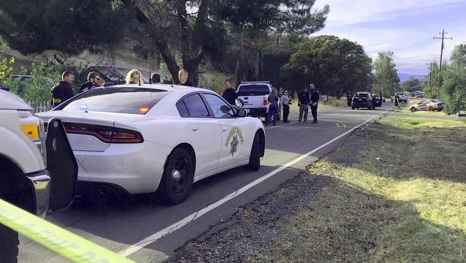 Law enforcement officials investigate a portion of Rancho Tehama Road where shooting suspect Kevin Neal was gunned down by police Tuesday.