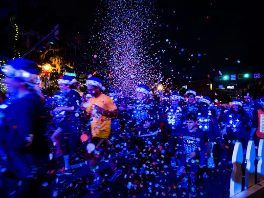 Runners head south on Monroe Street through confetti in the Jingle Bell Run, Saturday, at the 2017 City of Tallahassee Winter Festival, December 2, 2017