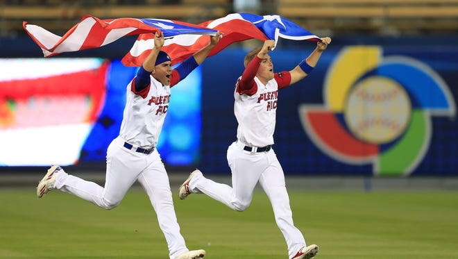 Hiram Burgos and Kike Hernandez carry Puerto Rico's flag as they celebrate their victory over the Netherlands.