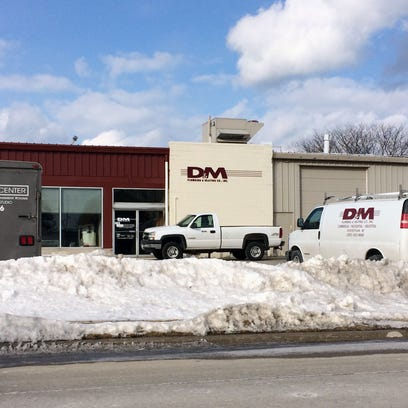 Vehicles are parked outside D&M Plumbing's 3411 Lakeshore Road location Tuesday. The company is seeking protection under Chapter 11, according to court filings.