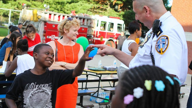 Antonio-Jovann Francois and Lt. Dan Gannon play around during an open house at Veazie Street Elementary School in Providence, R.I. The Providence Police Department's use of the High Point Strategy has helped clean up two neighborhoods that were synonymous with drug dealing and violence.