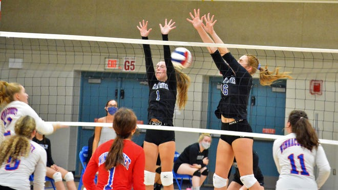 Oyster River's Emilia Cavicchi, left, and Kim Gowell go up for a block on Winnacunnet's Emily Graceffa during Monday's volleyball match in Hampton.