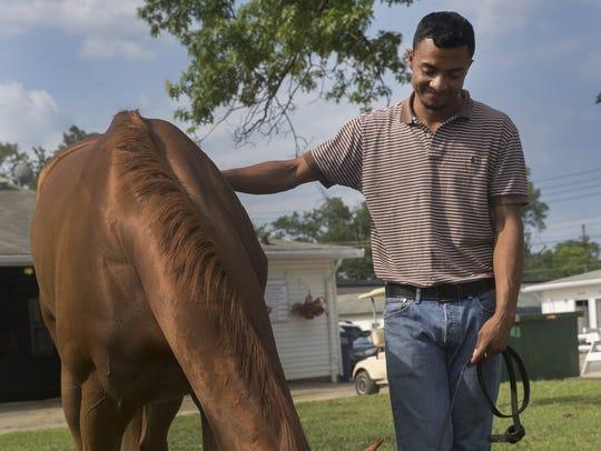 Flavio Alvarez watches over a horse as it grazes on