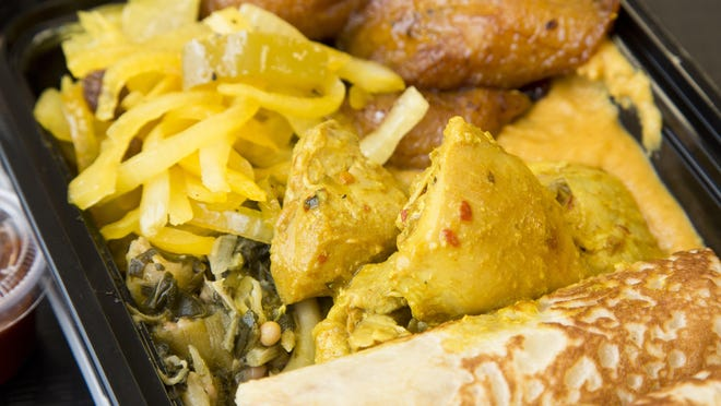 A plate filled with crepes, chicken suqqar, veggie mix, potato sauce, plantains, kud kud and red sauce at Afra Grill.