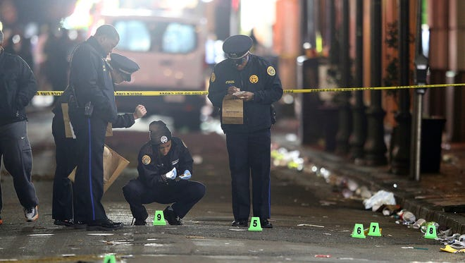 A crime scene technician collects a shell casing as New Orleans police investigate a fatal shooting at Iberville and Bourbon streets early Nov. 27, 2016.