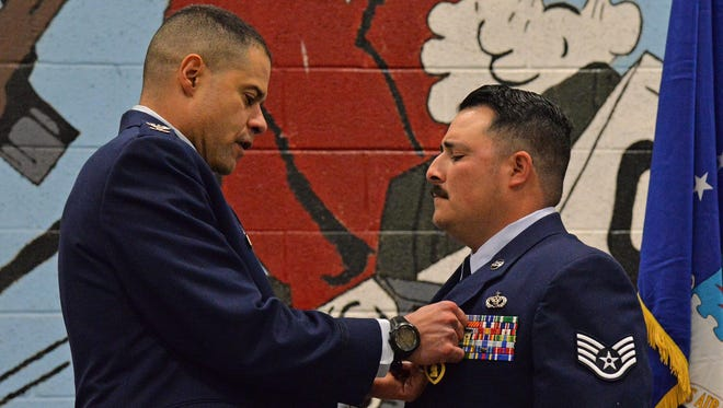 "Col. Rivera pins a Purple Heart medal on Staff Sgt. Dickison. ""That day in July 2009, (Dickison) and his teammates answered their nation's call while serving their country,"" Rivera said. ""There was a mission to be done. """