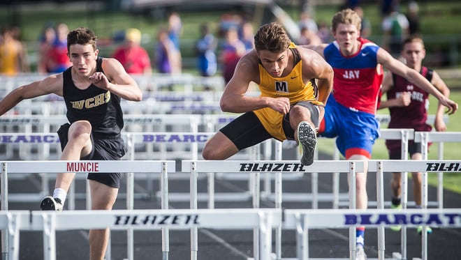 Monroe Central's Nick Mitchell, center, jumps over a hurdle in the boys track sectional at Central Thursday, May 17, 2018.
