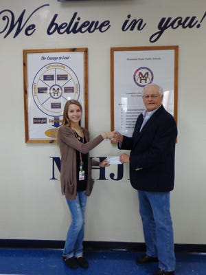 Cassandra Chipman, left, receives a check from Butch Holligan, Elks Benevolence Committee member. The Mountain Home Elks Lodge No. 1714 recently awarded a $925 sponsorship to Chipman for her to participate in a one-week educational trip to Washington with fellow Mountain Home Junior High School students.