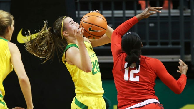 Oregon's Sabrina Ionescu, center, grabs a rebound to complete a triple-double at the end of third quarter.