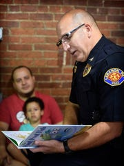 Aris Paulino holds his four-year-old son, Jaden, while Lebanon Chief of Police Todd Breiner reads to young people. Lebanon city Chief of Police Todd Breiner read 'Pout Pout Fish goes to School' to children at the Lebanon Farmer's Market Saturday, Aug. 20, in the inaugural 'Police, Read to Me' program. Joey Morrisey, hopes the program will be a regular third Saturday of the month event. Children were given a free book to take home, and several posed with Breiner before leaving.