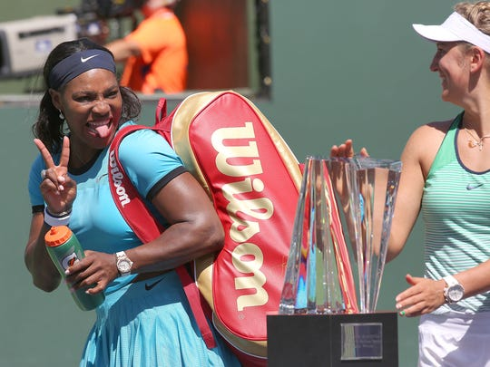 Serena Williams photobombs Victoria Azarenka's trophy photo at the BNP Paribas Open in Indian Wells, March 20, 2016.