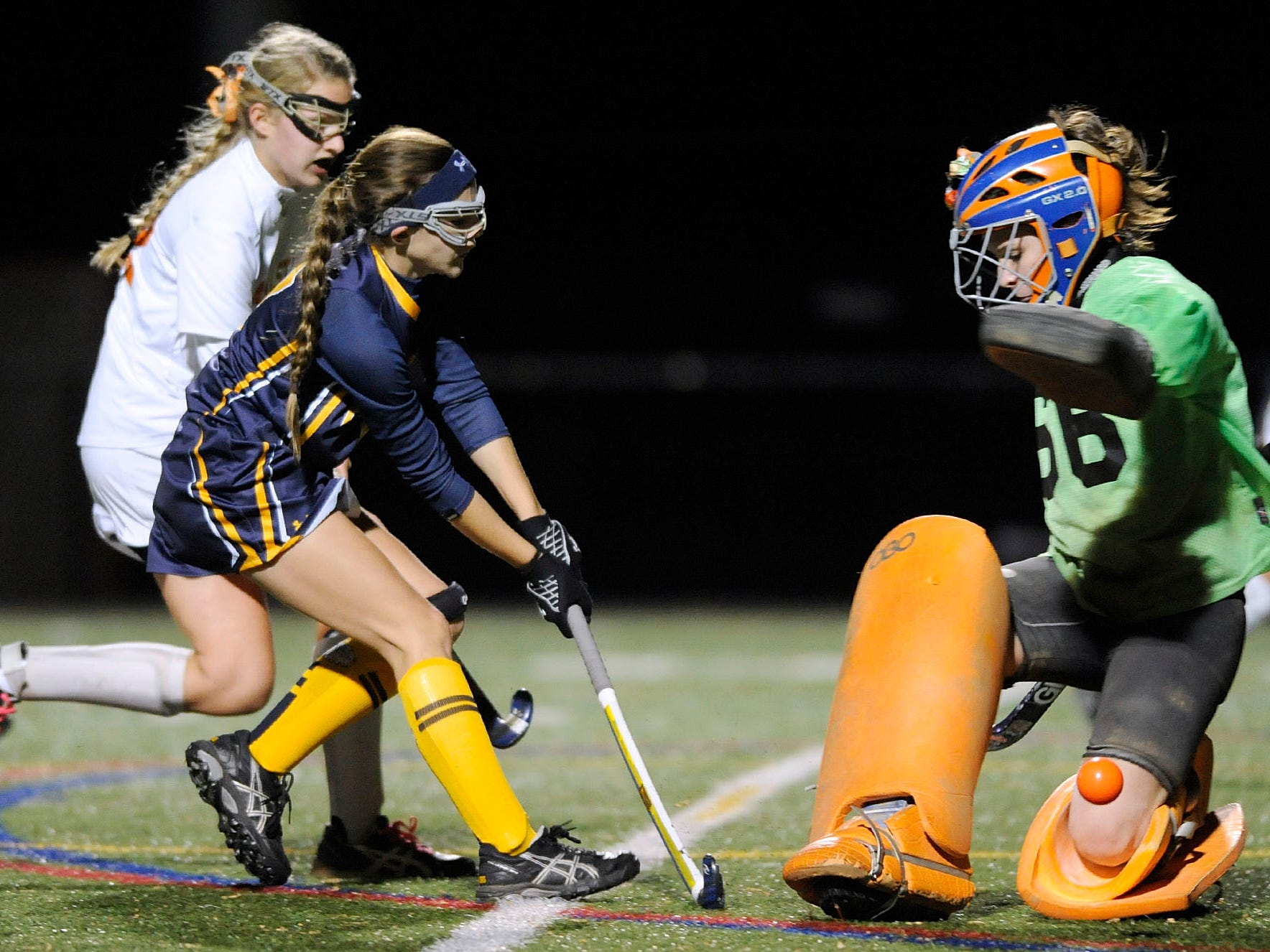 Pocomoke's Peyton Becker, second from left, trailed by Kate Bradley, left, hits a ball past Fallston goalkeeper Caitlin Phillips, right, in the first half of a state semifinal field hockey game Monday, Nov. 3, 2014 in Annapolis. Becker did not score on the play. (Photo by Steve Ruark for The Daily Times)