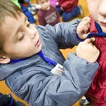 Firefighter J.D. Kulbeck helps Kiley Jay, 4, write her name on a coat during an Operation Warm event for Head Start children at Skyline School Tuesday.