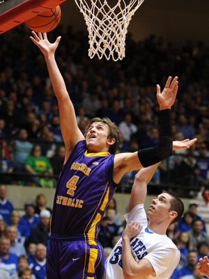 Guerin Catholic forward Matt Holba drives to the basket for a lay up against Greensburg during the Class 3A Semistate game, Saturday, March 22, 2014, inside the Tiernan Center at Richmond High School.