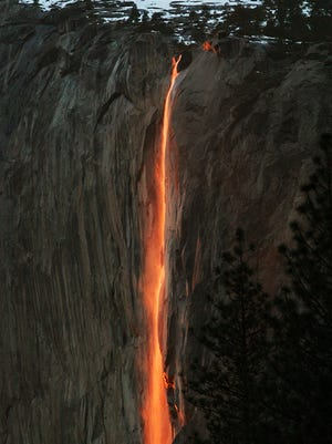 In this Feb. 16, 2010, file photo, a shaft of sunlight creates a glow near Horsetail Fall, in Yosemite National Park, Calif. Mother Nature is again putting on a show at California's Yosemite National Park, where every February the setting sun draws a narrow sliver on a waterfall to make it glow like a cascade of molten lava.